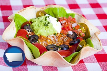 a texmex taco salad in a baked tortilla - with Montana icon