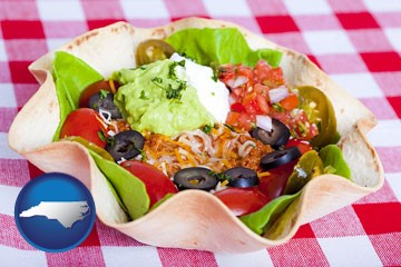 a texmex taco salad in a baked tortilla - with North Carolina icon